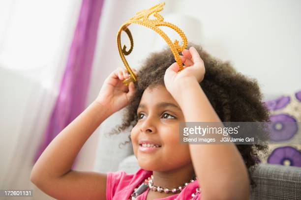african american girl putting on toy crown - princess stock pictures, royalty-free photos & images