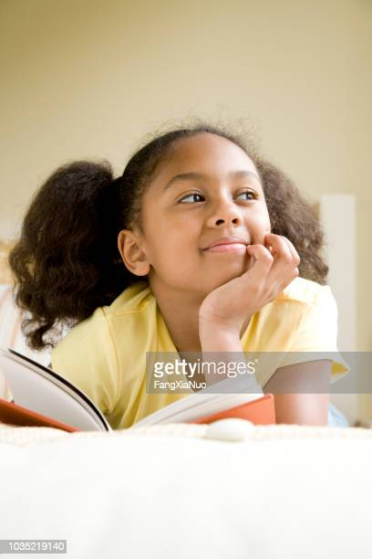 african american girl reading book in bed - hand on chin stock pictures, royalty-free photos & images