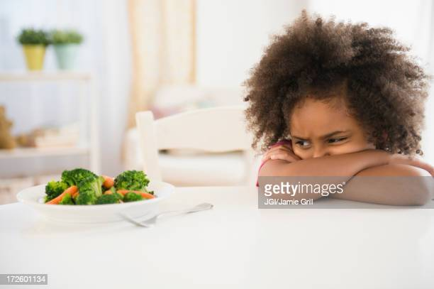 african american girl refusing vegetables at table - refusing stock pictures, royalty-free photos & images