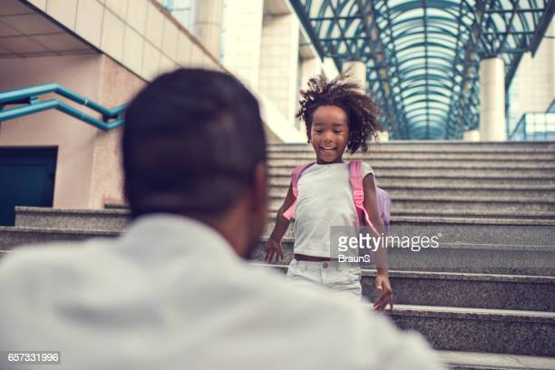 African American girl running down the stairs to her father.