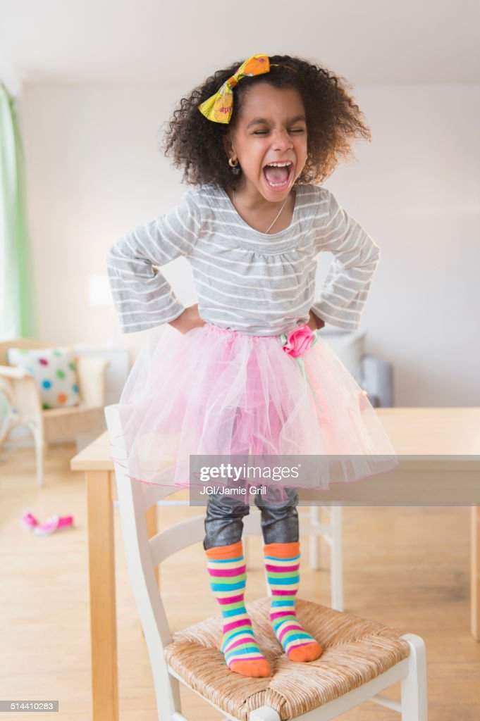 African American girl shouting on chair : Stock Photo