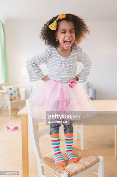 African American girl shouting on chair