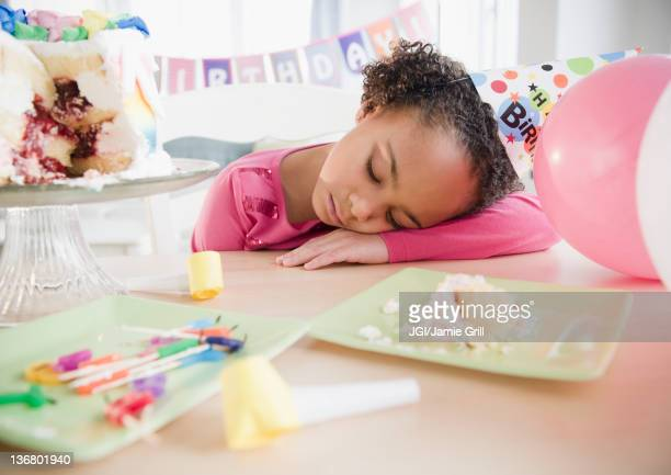 African American girl sleeping at birthday party