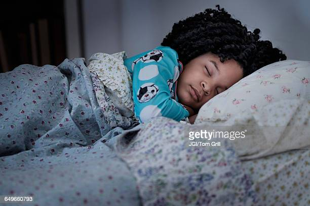 African American girl sleeping in bed