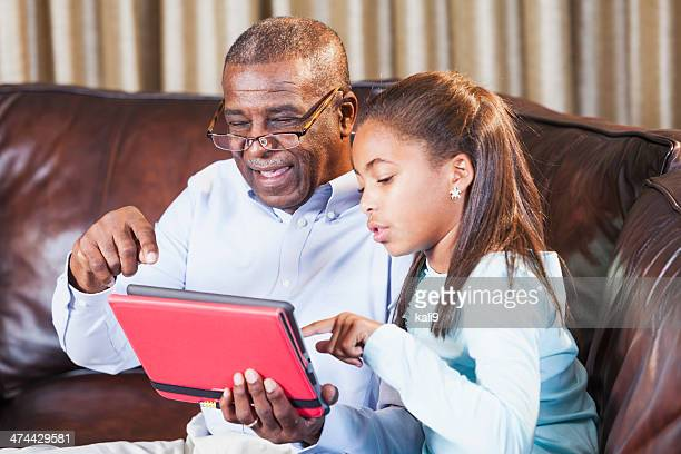 African American girl teaching grandfather to use digital tablet