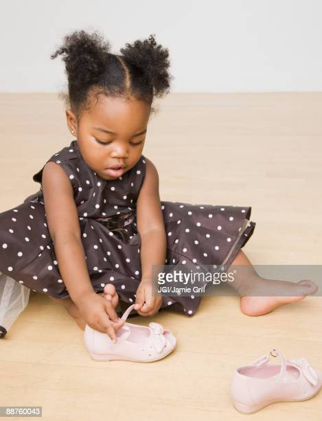 African American girl trying to put shoes on