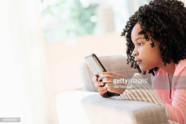 African American girl using cell phone on sofa