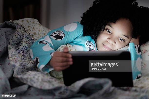 African American girl using digital tablet in bed