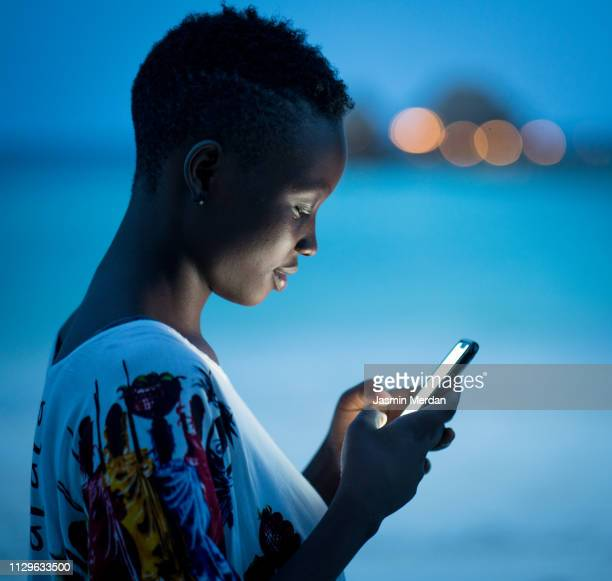 african american girl using mobile phone on night beach - femme africaine photos et images de collection