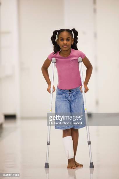 African American girl walking on crutches