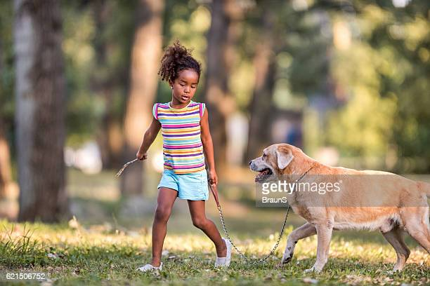 African American girl walking with her dog in the park.