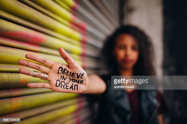 african american girl with inspirational meassage written on her hand - opstand stockfoto's en -beelden