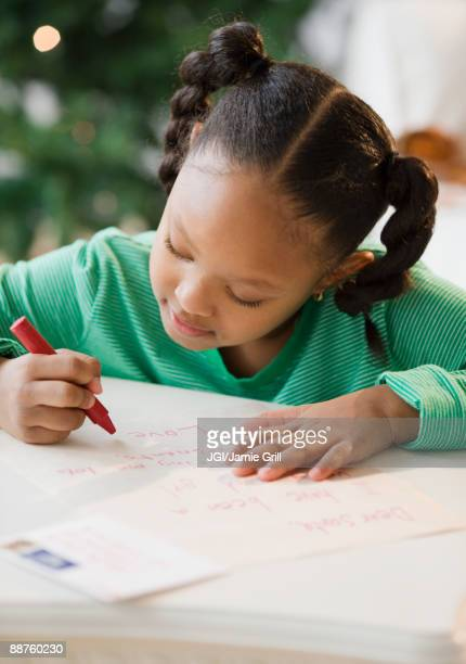 African American girl writing letter to Santa Claus