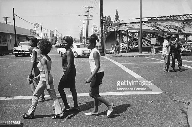 African American girls cross the road near Central Avenue near the ruins of a shop destroyed in the race riots Los Angeles August 1965