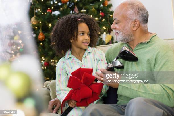 African American granddaughter giving grandfather Christmas gift