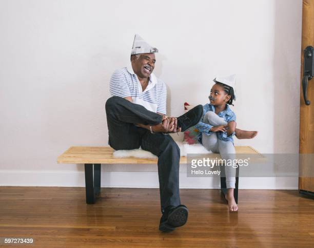 African American grandfather and granddaughter playing on bench