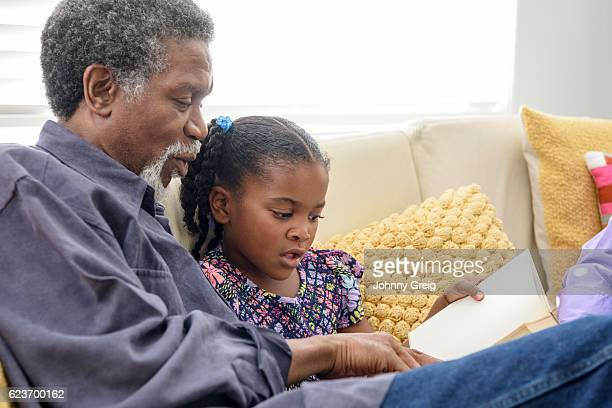 African American grandfather listening to girl read book