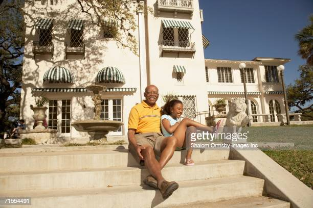 African American grandfather sitting with granddaughter outdoors