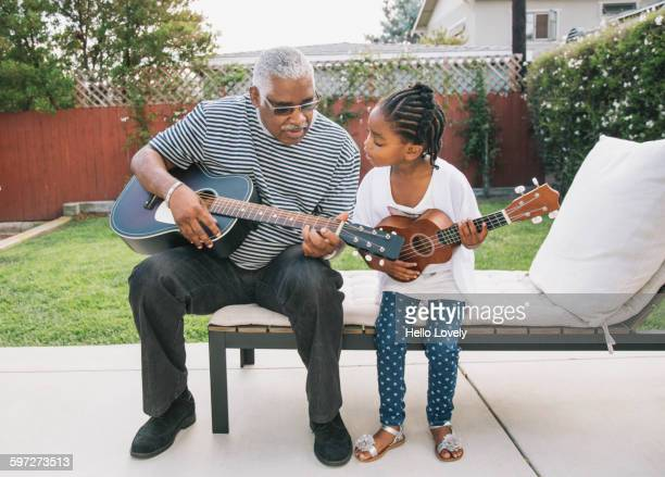 African American grandfather teaching granddaughter to play guitar