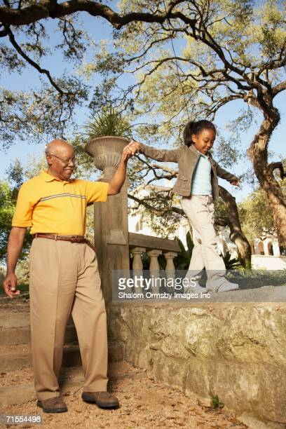 African American grandfather walking with granddaughter