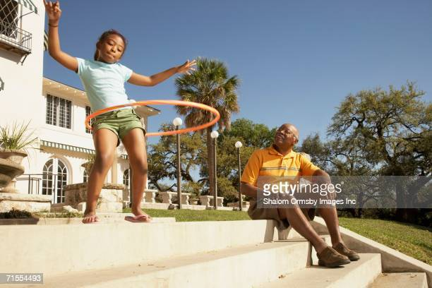 african american grandfather watching granddaughter hula hoop - black photos et images de collection