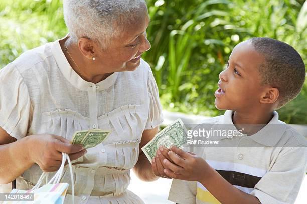 African American grandmother handing money to grandson