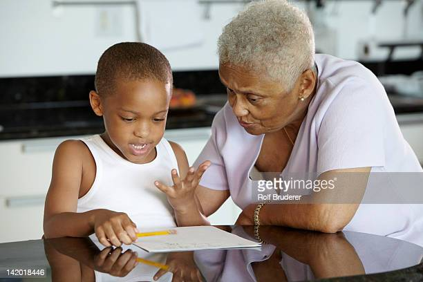 African American grandmother helping grandson with homework