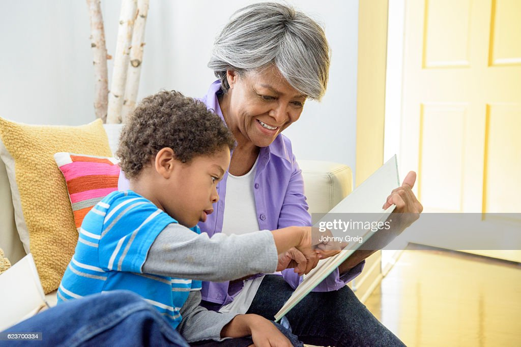 African American grandmother showing book to grandson, smiling : Foto de stock