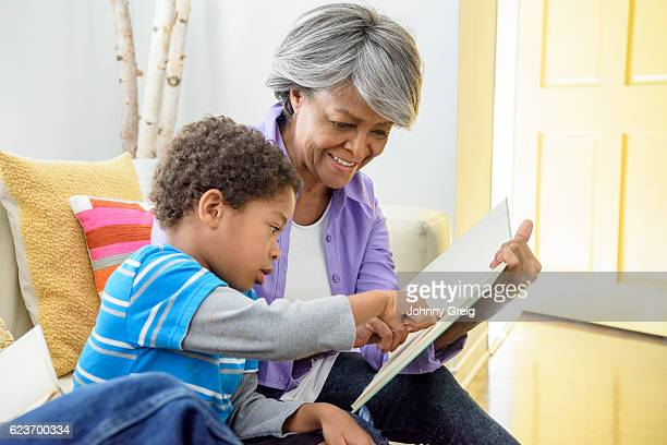 African American grandmother showing book to grandson, smiling