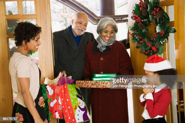 African American grandparents arriving with Christmas gifts