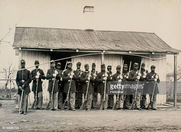 African American guards of the 107th United States Colored Troops pose putside a guard house at Fort Corcoran