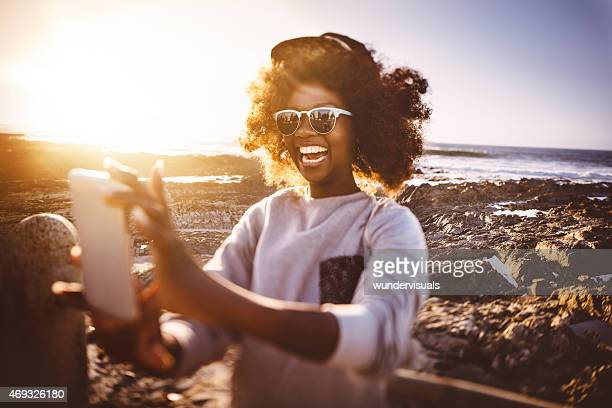 African American hipster teen girl taking selfie at the beach