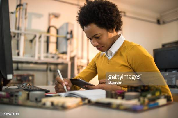 african american it technician taking notes while using digital tablet. - power occupation stock photos and pictures