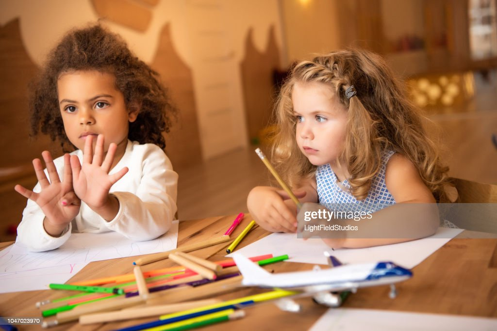 african american kid showing number nine with fingers in kindergarten : Stock Photo