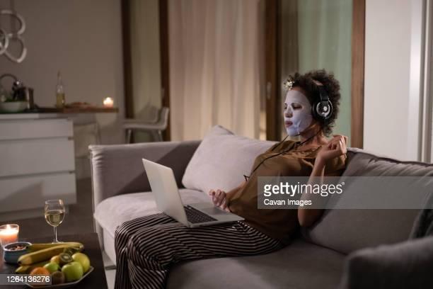african american lady in sheet mask using laptop - film oder fernsehvorführung stock-fotos und bilder