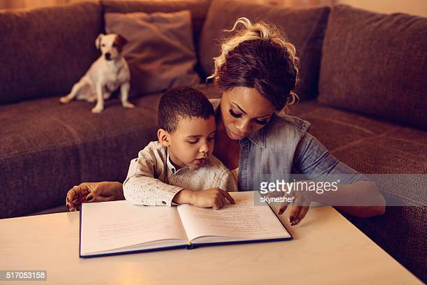 African American little boy and his mother reading a story.