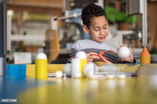 African American little boy building something in laboratory for school science project.