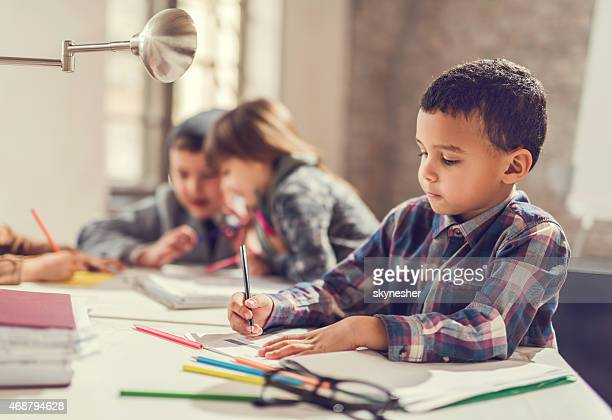 African American little boy sketching.