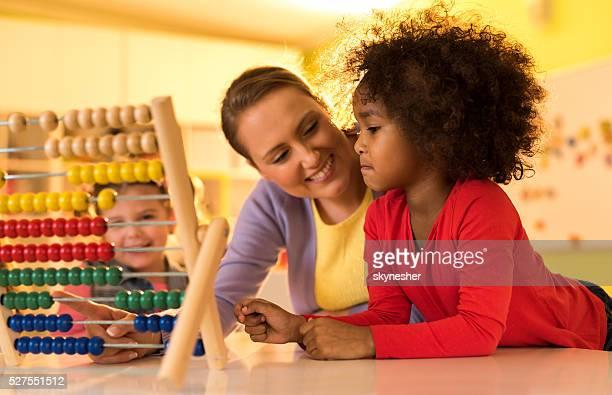 Afrikanische amerikanische kleines Mädchen und Lehrer mit abacus bereits im kindergarten an.