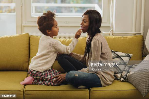 African American little girl applying lipstick on mother's lips.
