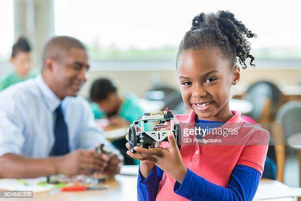 African American little girl using robotics during science class