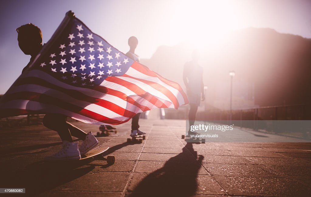 African American longboarder flying an American flag : Stock Photo