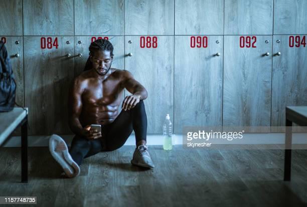 ロッカールームで携帯電話を使用してアフリカ系アメリカ人の男性アスリート。 - ロッカールーム ストックフォトと画像