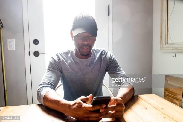 african american man controleert zijn telefoon - werkloosheid stockfoto's en -beelden