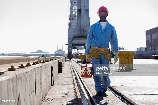 African American male construction worker carrying toolbox