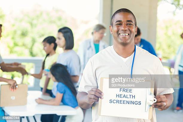 african american male nurse promotes community health fair - film and television screening stock pictures, royalty-free photos & images