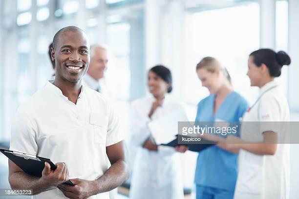 African American enfermero con el equipo médico en el fondo