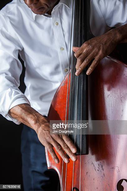 African American man 60's playing a double bass