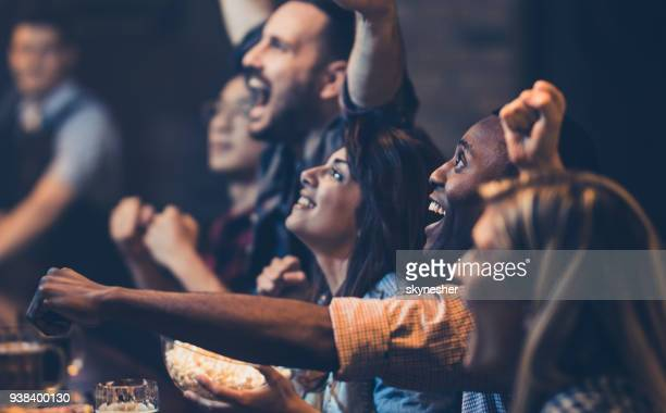 african american man and his friends cheering while watching a game in a bar. - cheering stock pictures, royalty-free photos & images