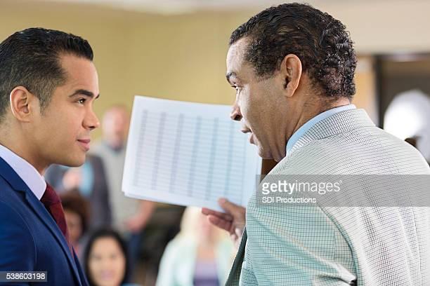 Afroamerikanischer Mann und Hispanic Mann papework besprechen